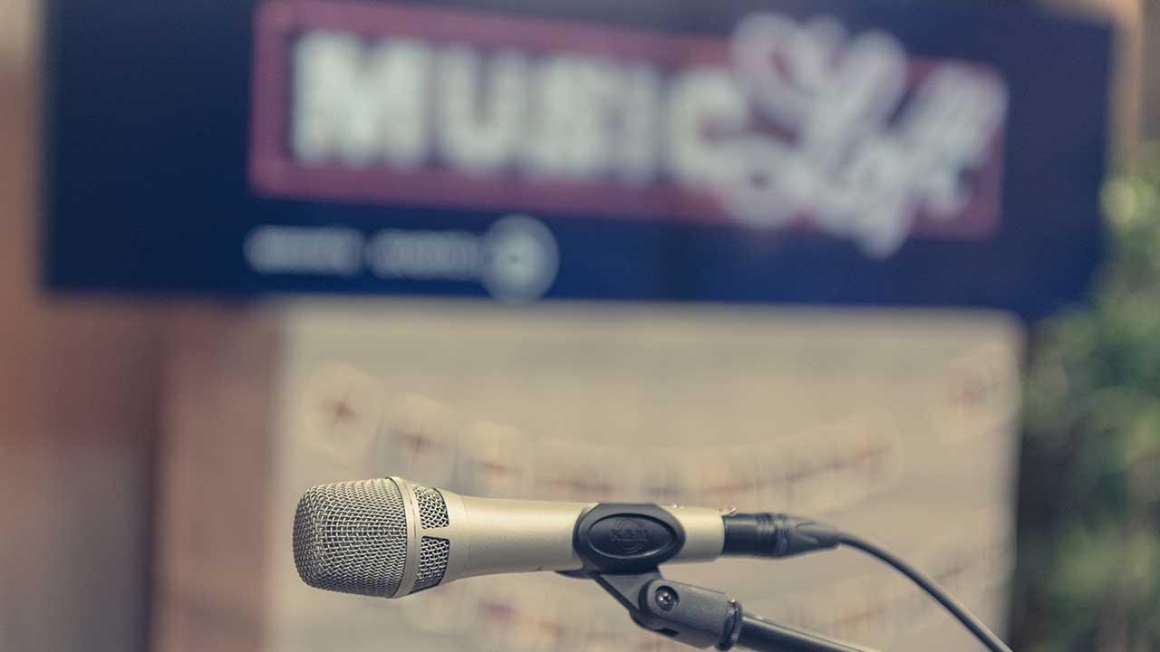 Schriftzug der Music Loft mit einem Mikrofon