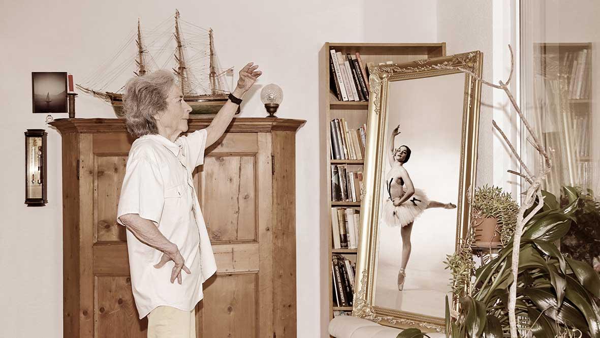 Seniorin mit ihrem jüngeren Spiegelbild im Rahmen der Ausstellung «WÄRTvou im Alter»