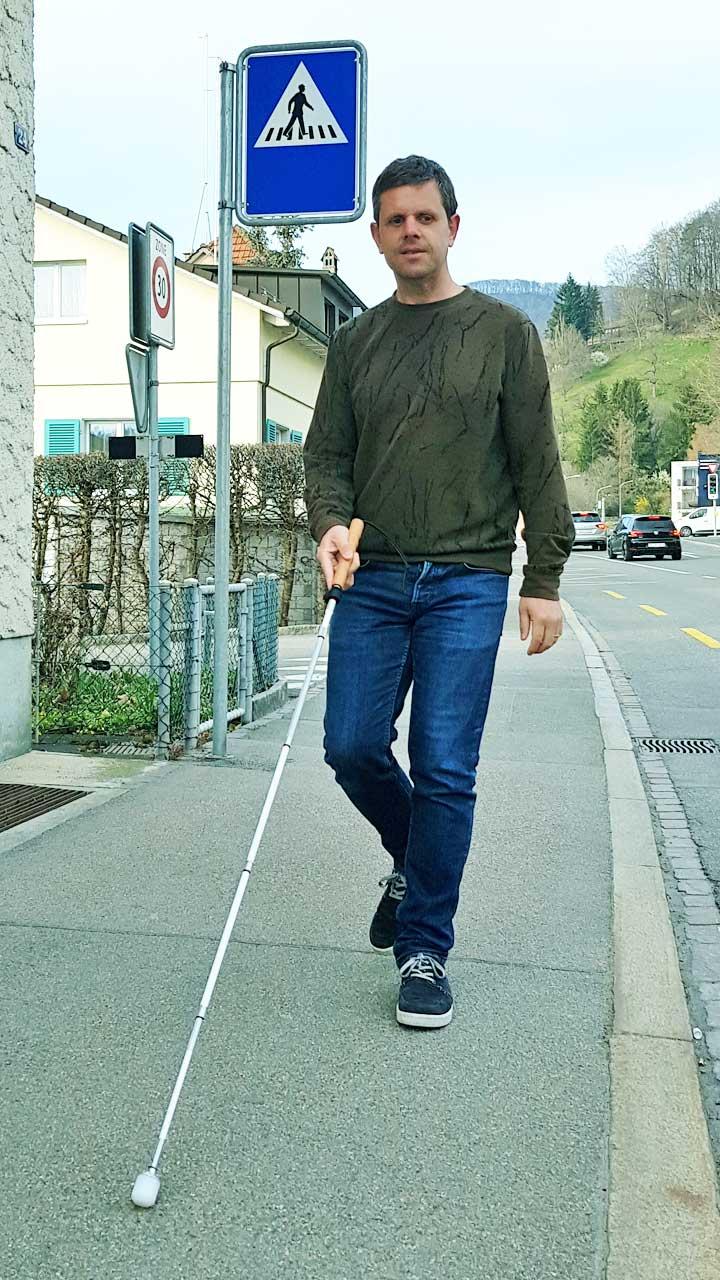 Der blinde Marco Jörg unterwegs auf einem Trottoir