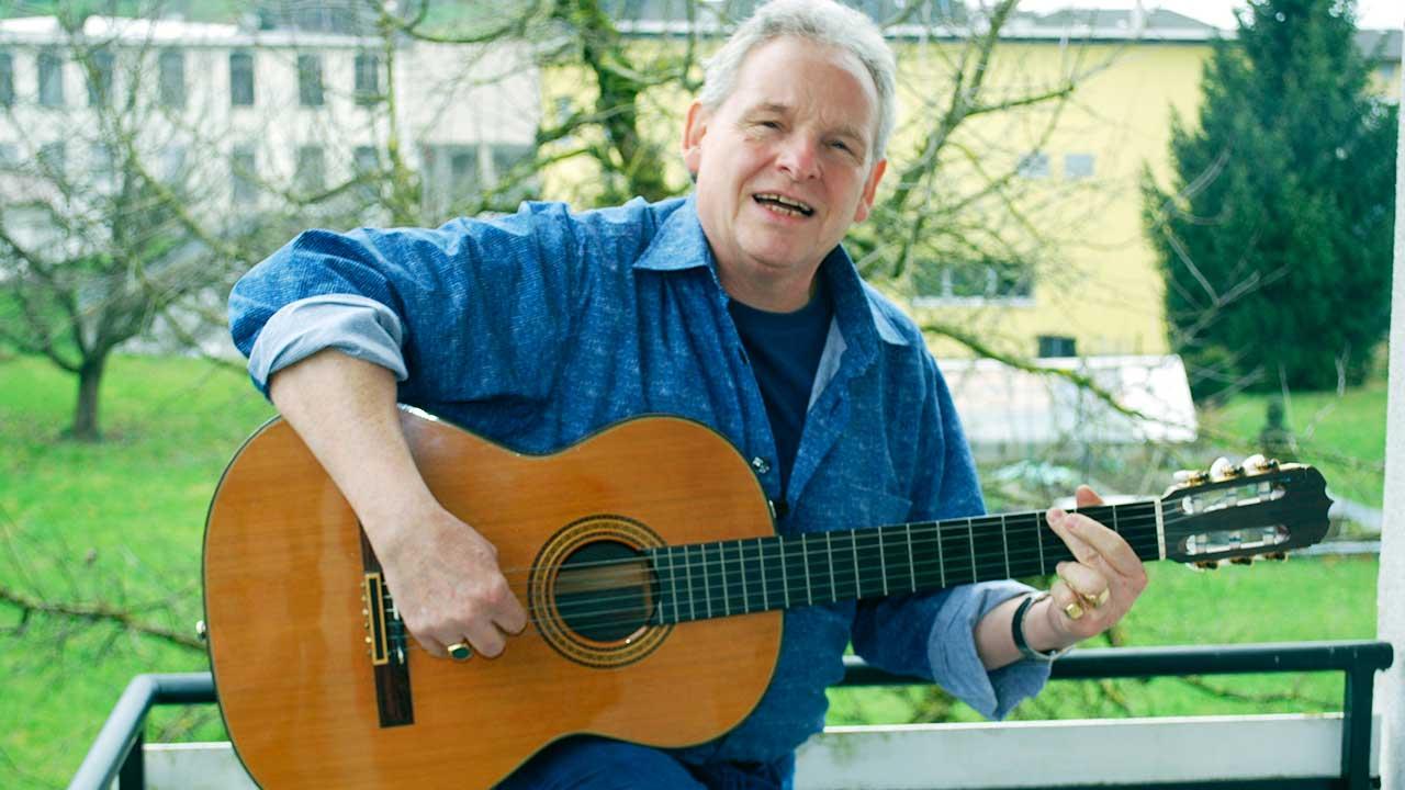 Roland Pöschl mit seiner Gitarre auf dem Balkon