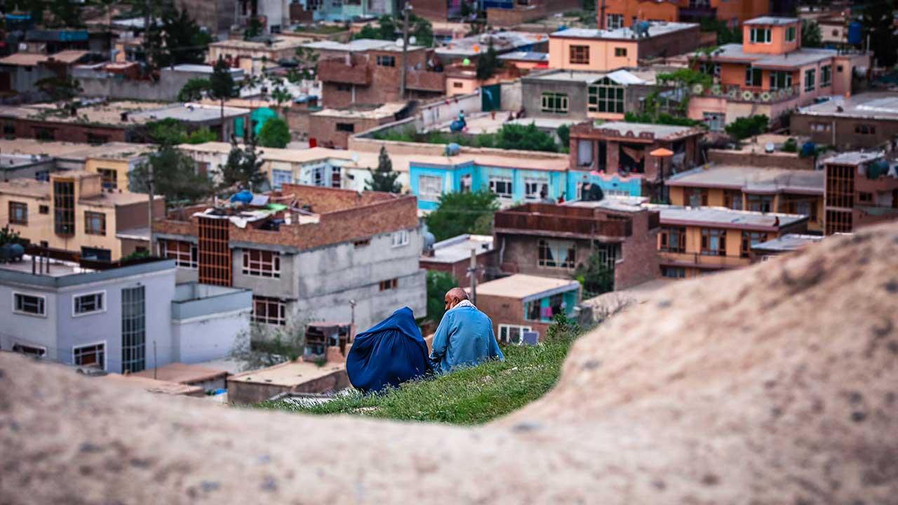 Ein Paar sitzt auf einem Felsen und blickt auf Häuser von Kabul