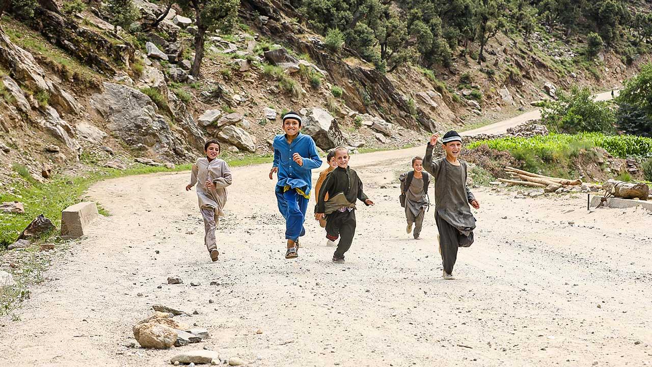 Afghanische Knaben rennen eine Strasse entlang