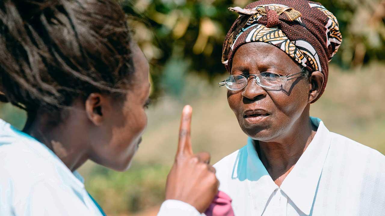 In Afrika: Jüngere Frau testet mit Zeigefinger, ob die ältere Frau die richtigen Brillengläser trägt