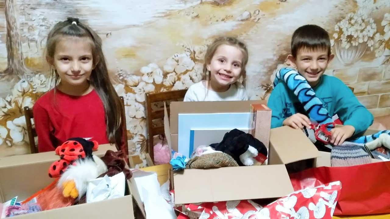 Drei glückliche Kinder bei der Aktion Weihnachtspäckli
