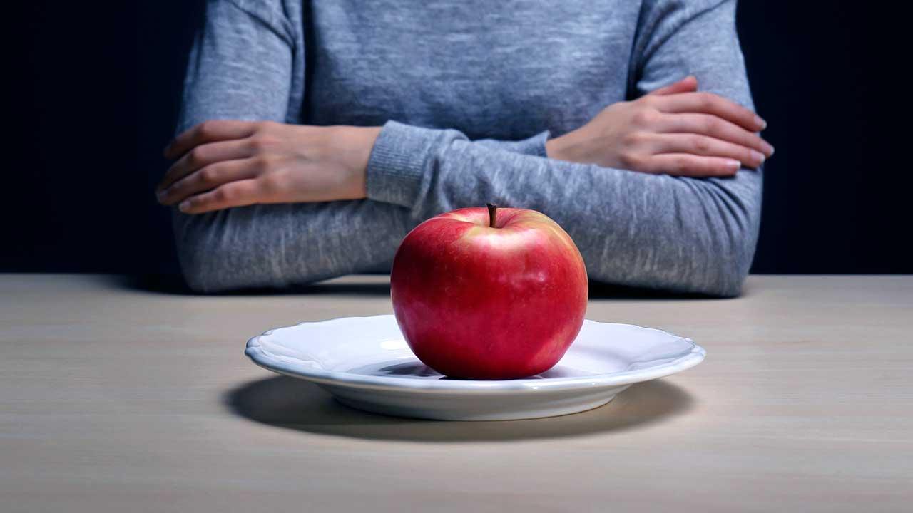 Frau sitzt mit verschränkten Armen vor einem Apfel