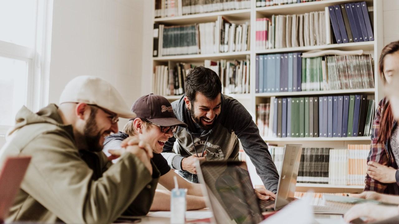 Drei Männer schauen lachend auf einen Bildschirm.