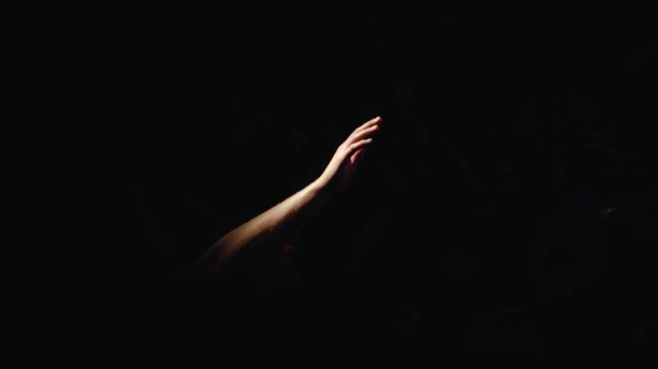 beleuchteter Arm in der Dunkelheit streckt sich nach oben zu Gott aus