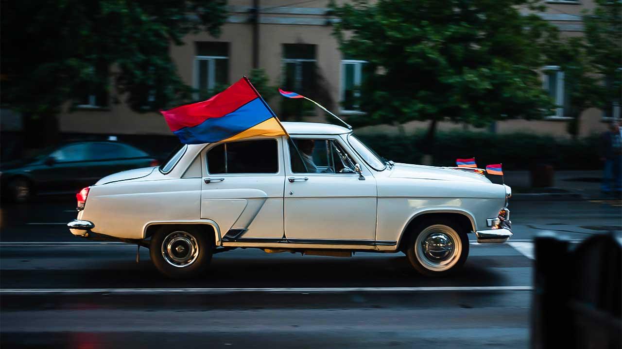 Auto mit armenischen Flaggen fährt durch Erewan