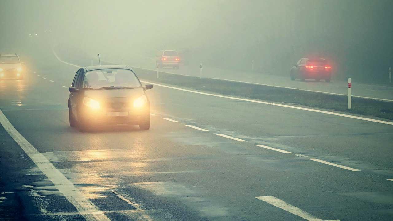 Autos mit eingeschalteten Scheinwerfern unterwegs auf einer nebligen Strasse