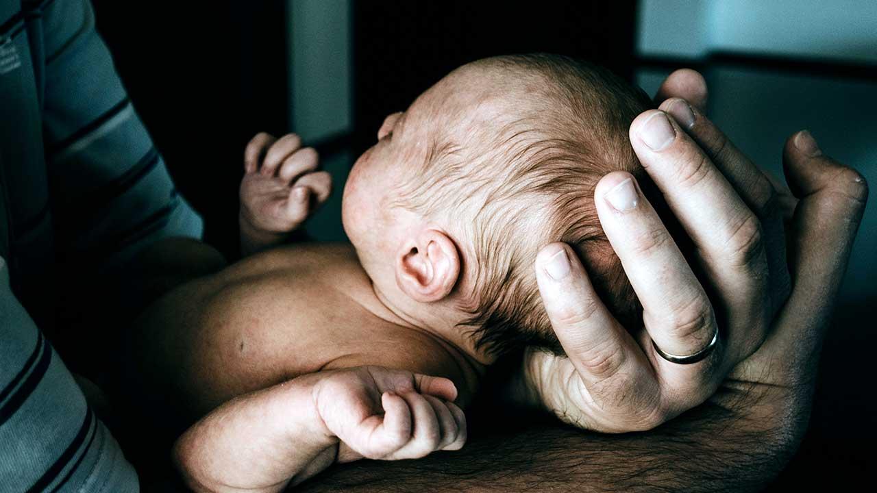 Baby in den Händen eines Mannes