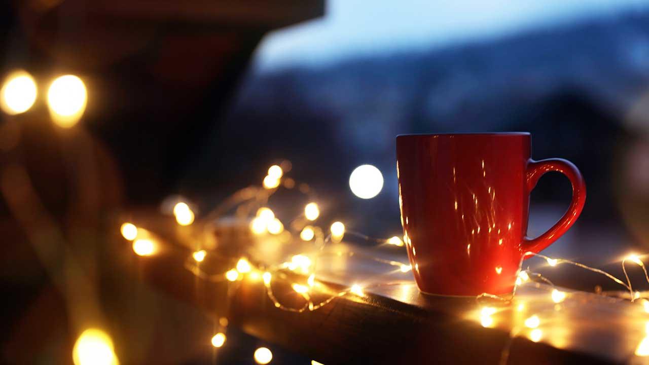 Balkon mit Lämpchen beleuchtet und mit roter Tasse