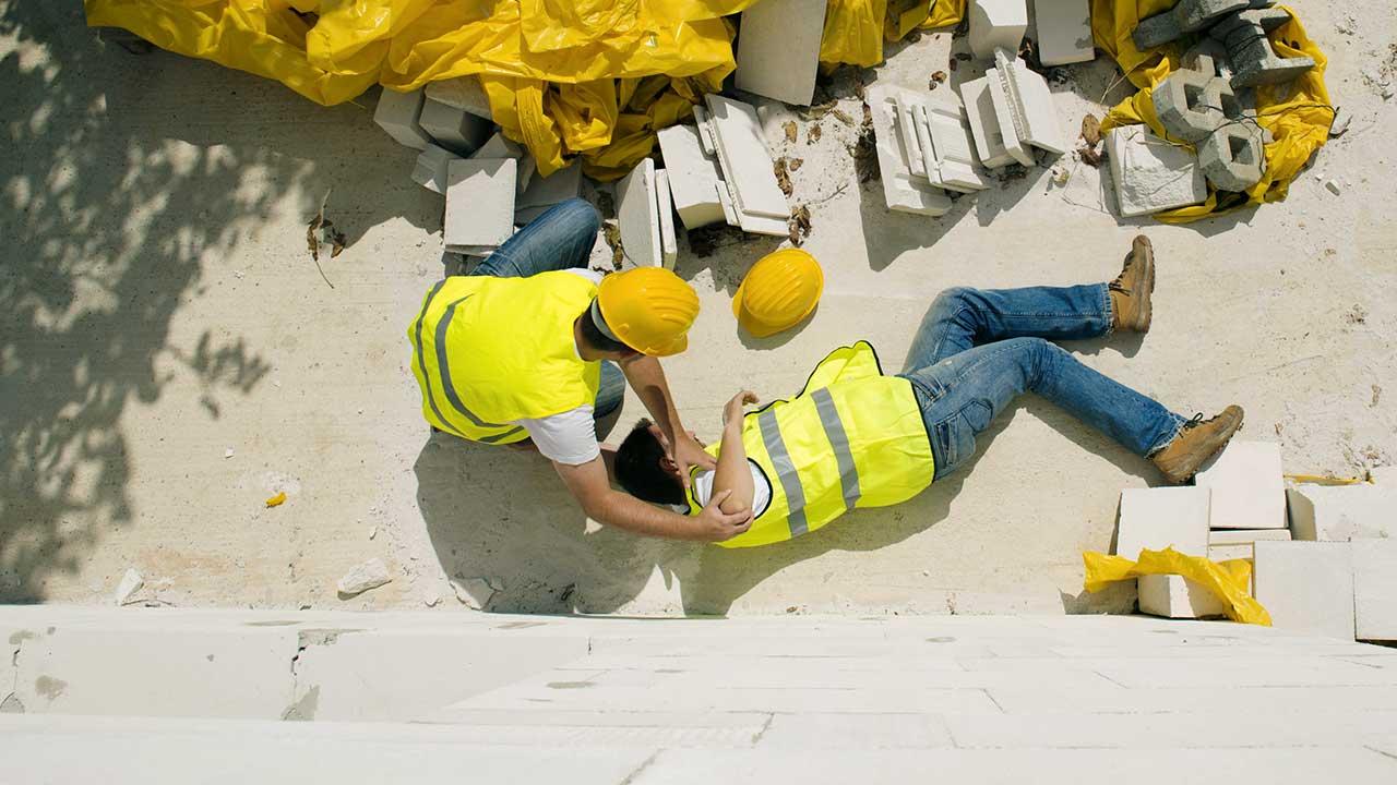 Zwei Bauarbeiter: Einer liegt verletzt am Boden, der andere hilft ihm.
