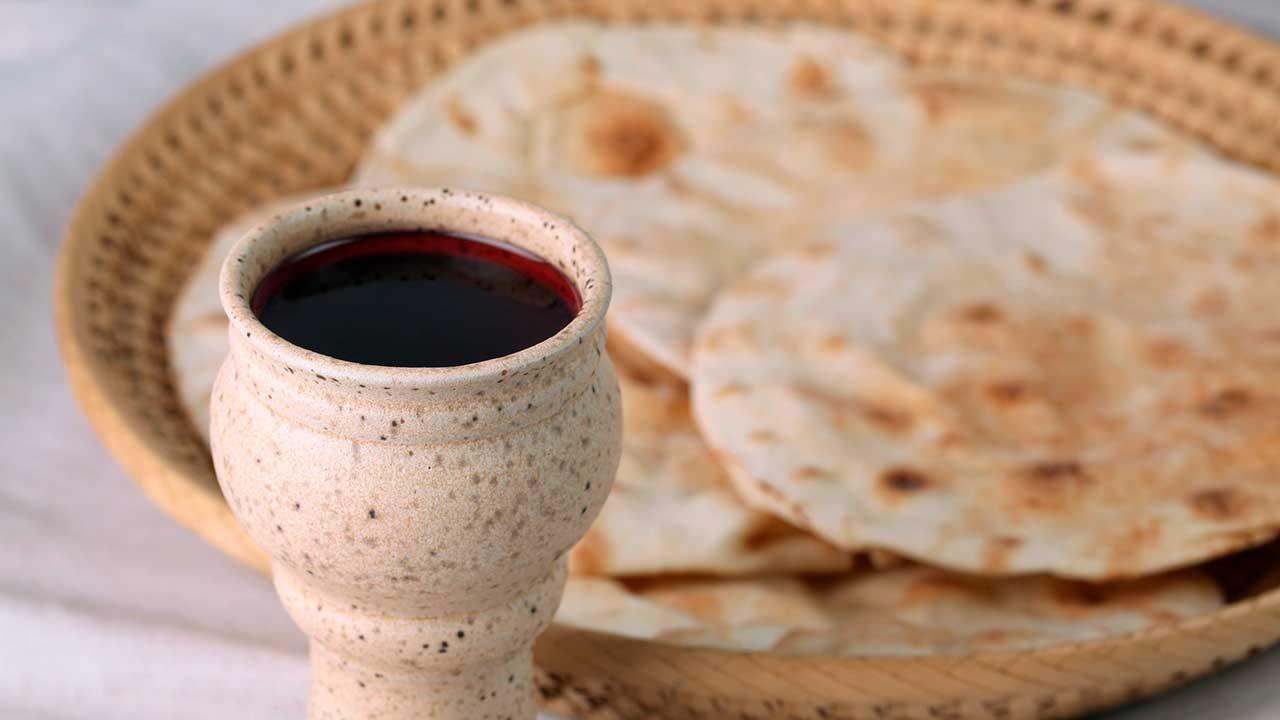 Becher mit Wein und Fladenbrot als Symbole für das Abendmahl