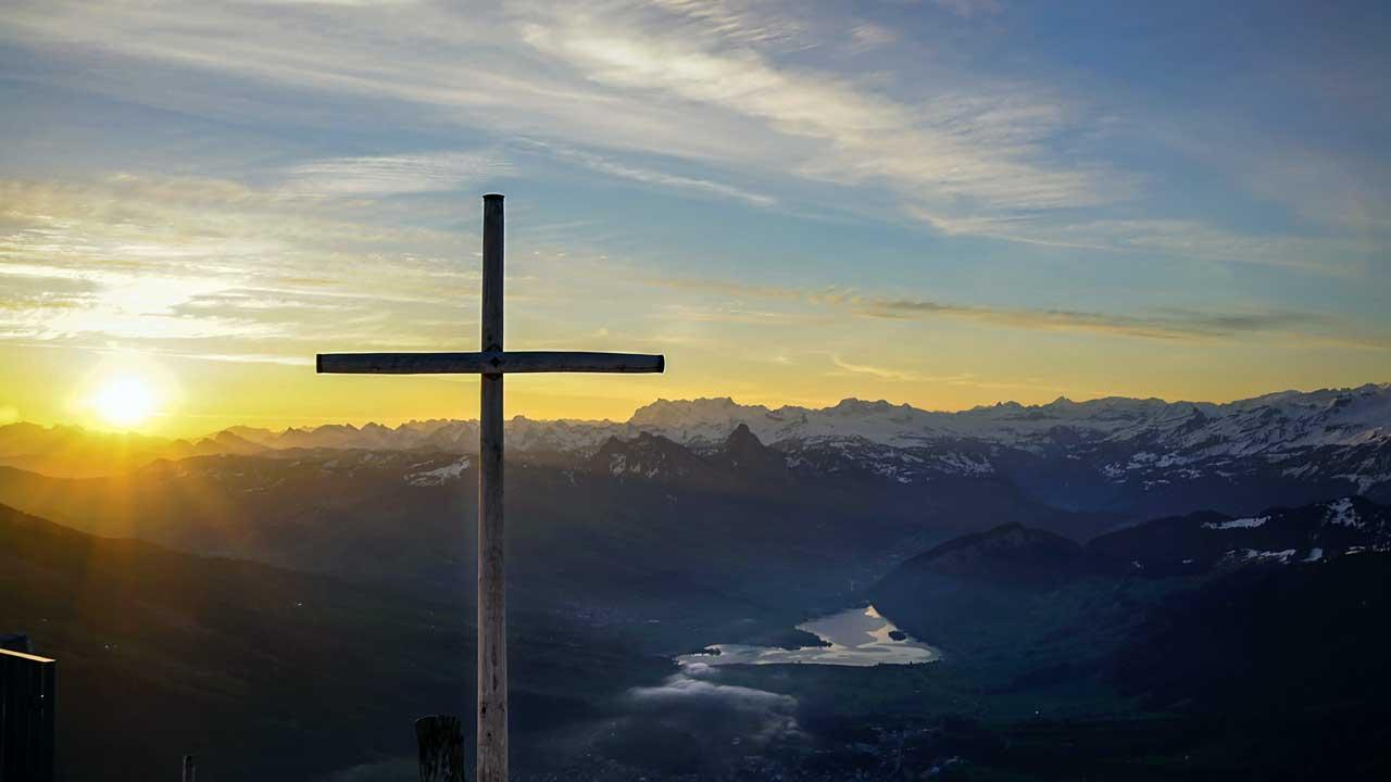 Kreuz in den Bergen mit Sonnenaufgang