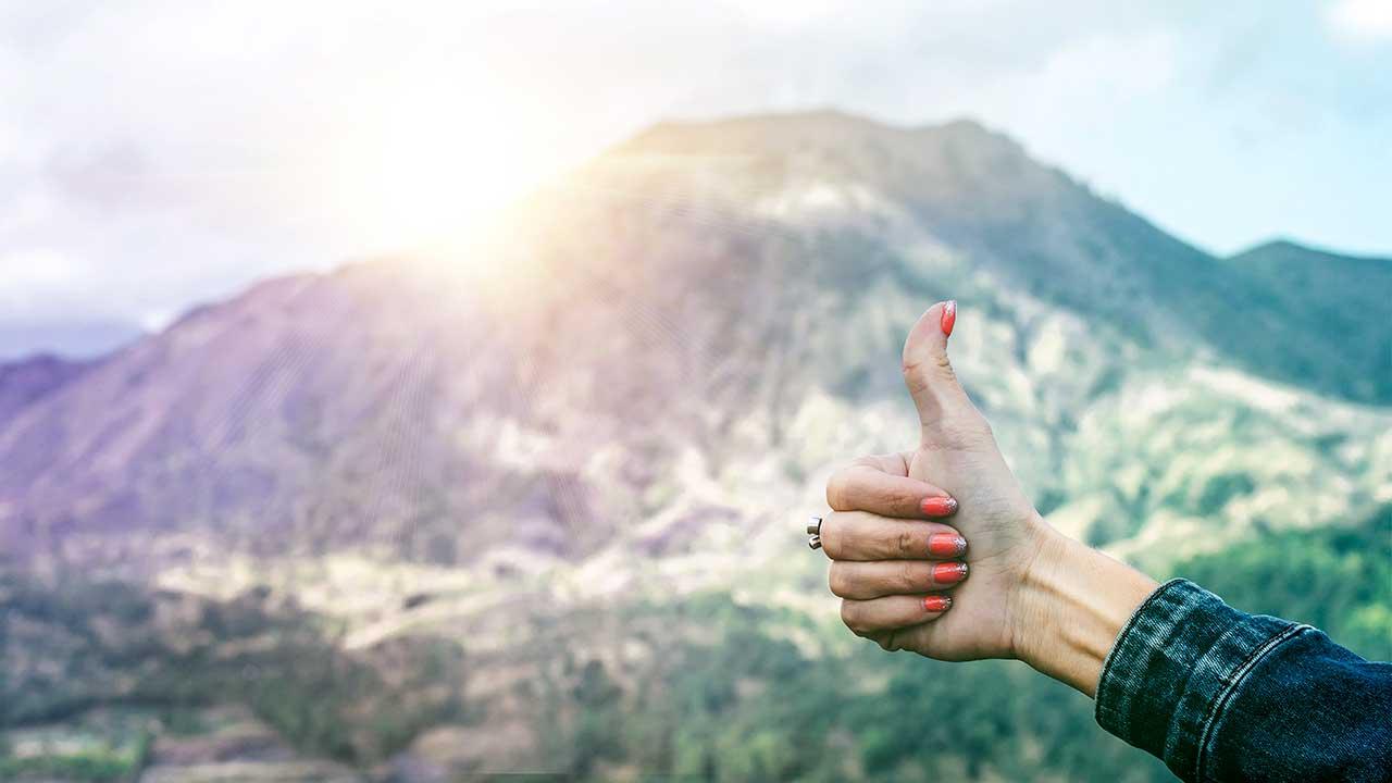 Hand mit Daumen hoch und Sonnenlicht über dem Berghorizont