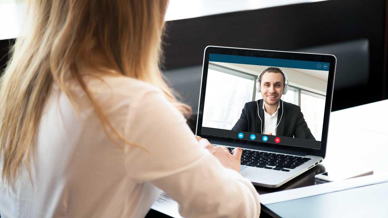 Frau führt mit Mann im beruflichen Umfeld ein Videogespräch