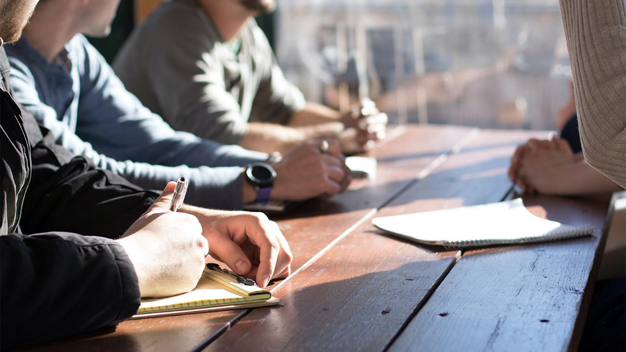 Leute sitzen zusammen an einem Tisch | (c) unsplash