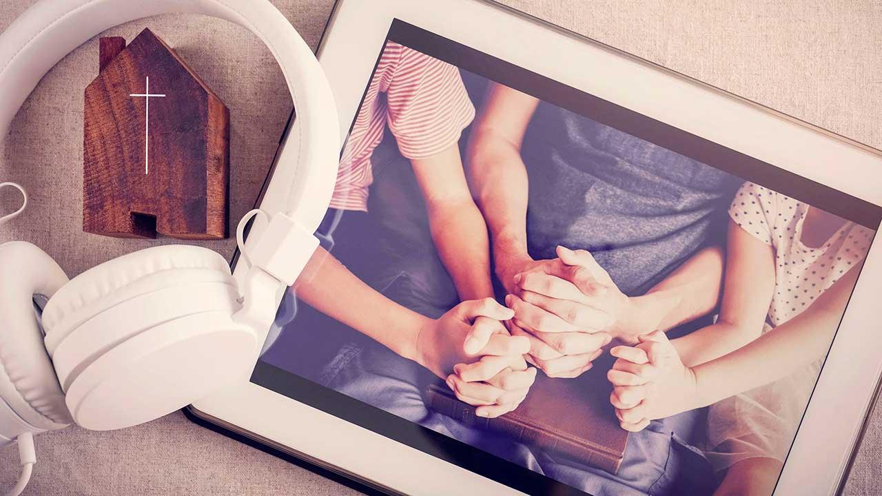 Tablet zeigt betende Hände in einer Gebetsrunde
