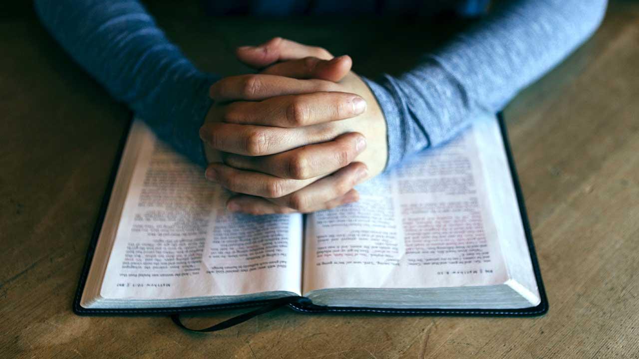 Gefaltete Hände beim Gebet auf einer Bibel