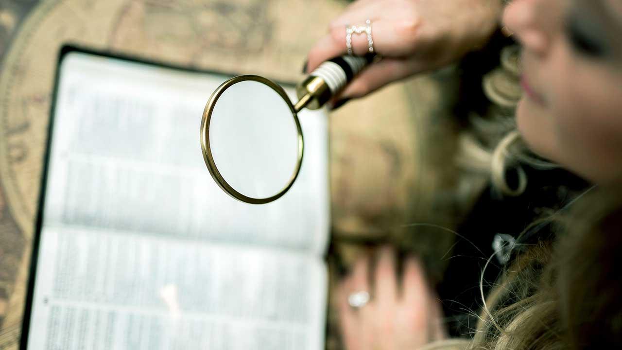 Frau hält eine Lupe über eine offene Bibel