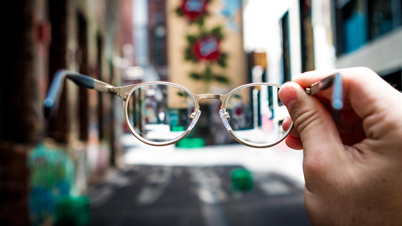 Eine Hand hält eine Brille, im Hintergrund sieht man die Strasse einer Stadt.