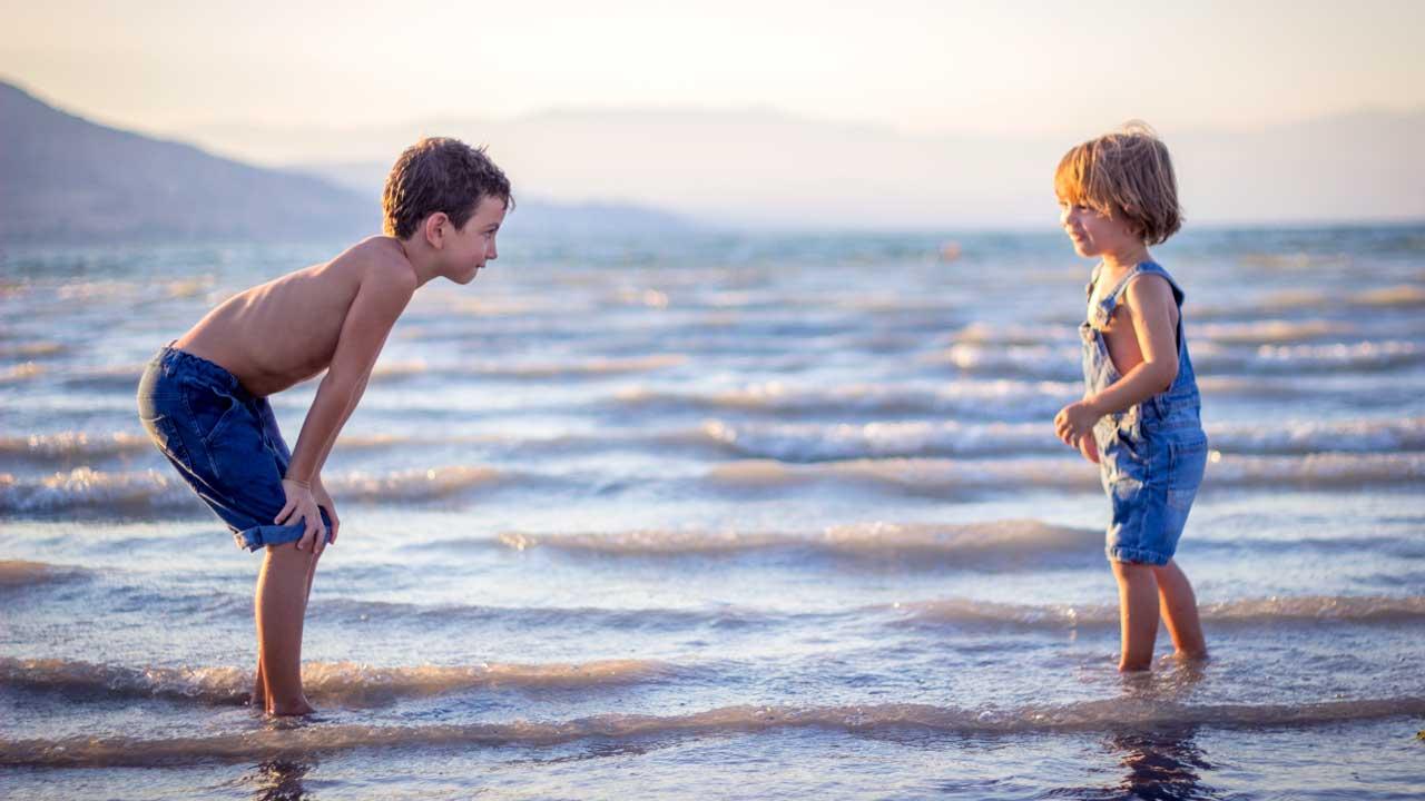 Zwei Brüder stehen sich am Strand gegenüber