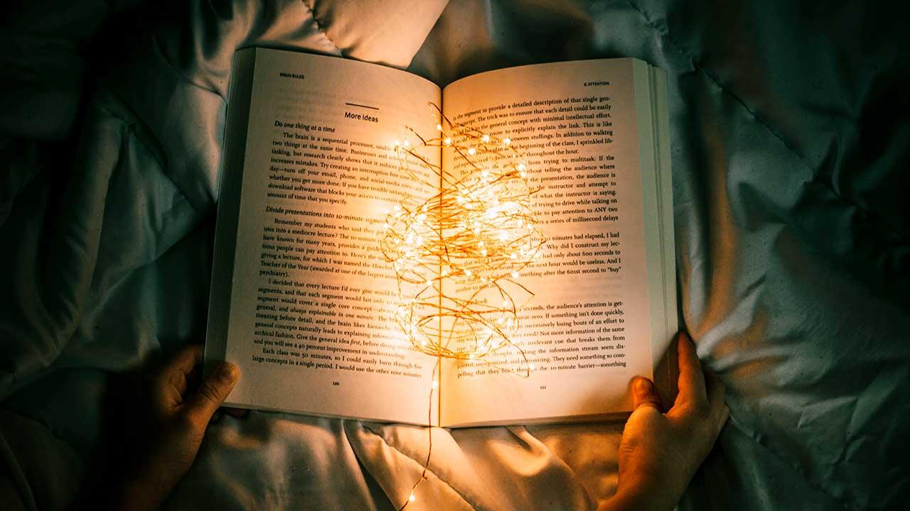 Geöffnetes Buch, darauf ein Kabel mit kleinen Lichtlein