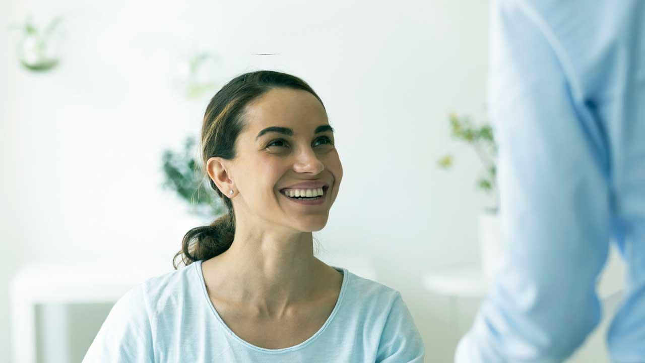 Frau sieht lächelnd zu einem Kollegen hoch