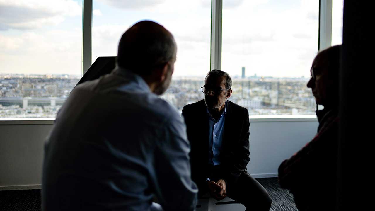 Drei Männer führen in einem Büro ein Gespräch miteinander.
