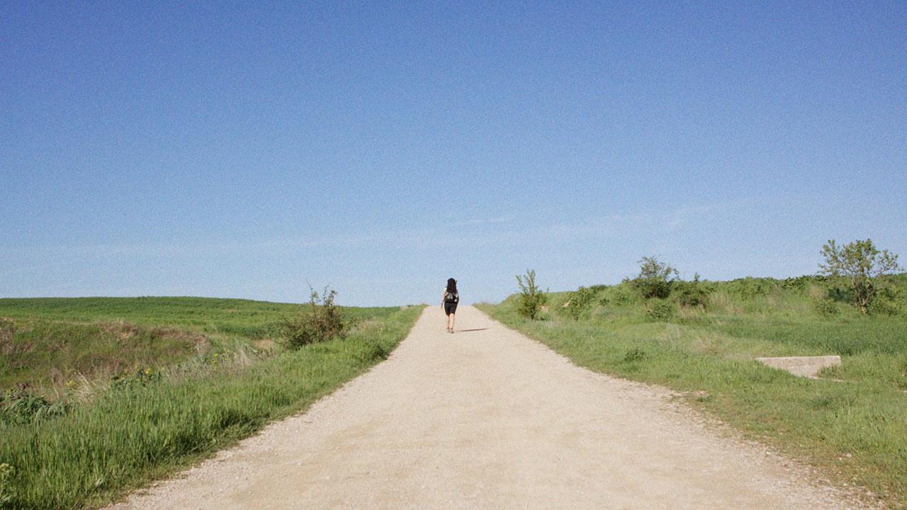 Eine Person auf einem langen Weg.
