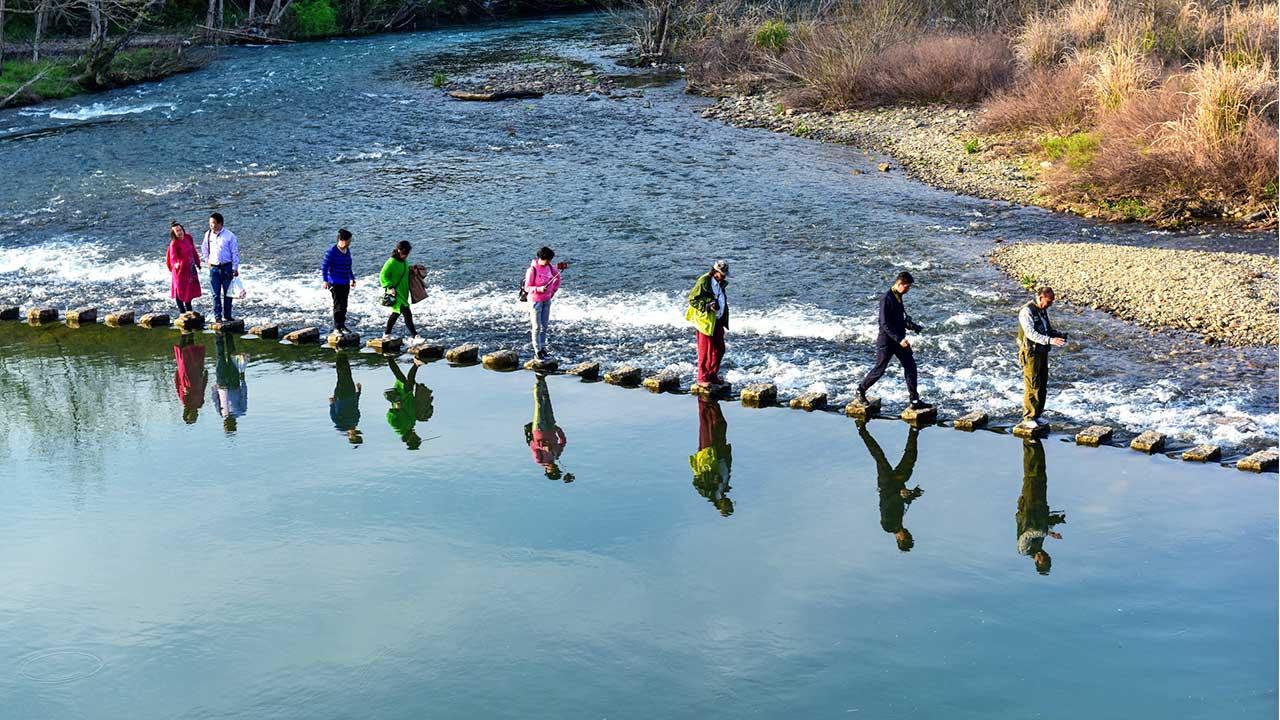 Von Stein zu Stein: Menschen laufen auf der Regenbogen-Brücke in Jianxi, China
