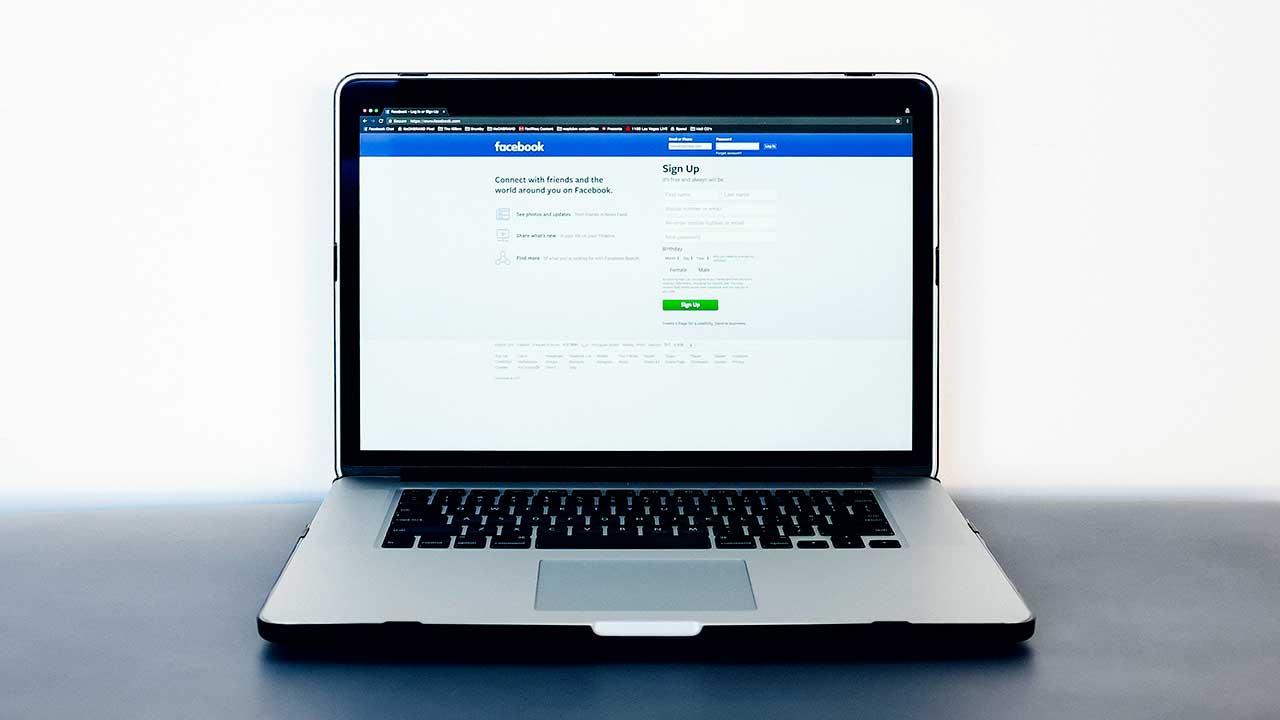 Aufgeklappter silberner Laptop mit Startseite von Facebook