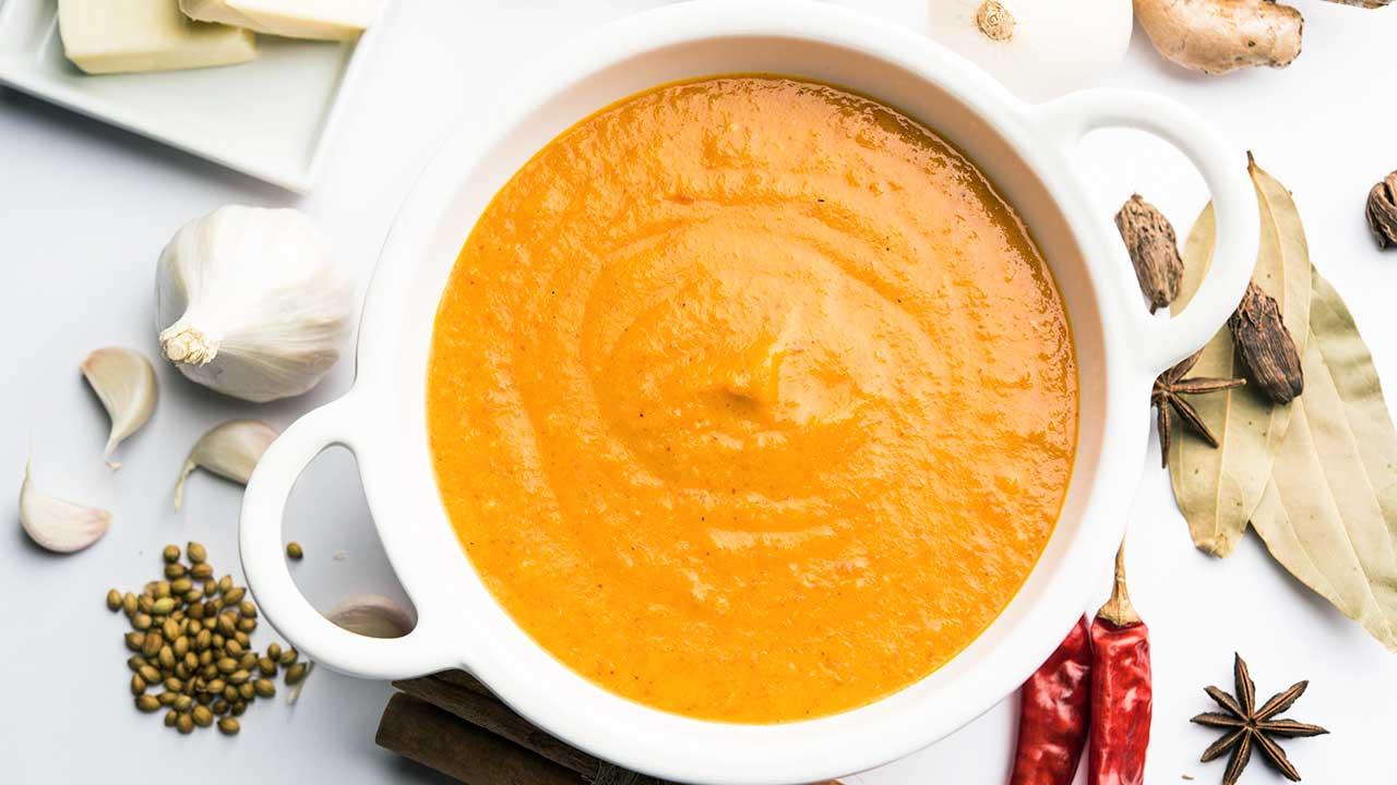 Currysuppe in einer weissen Schüssel, darum herum Zutaten
