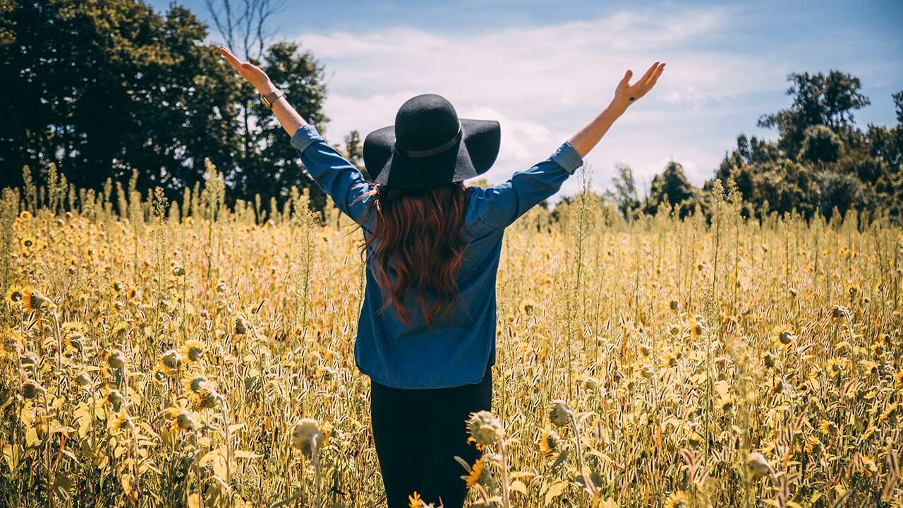 Eine Frau steht auf einem Feld und hebt ihre Hände zum Himmel.