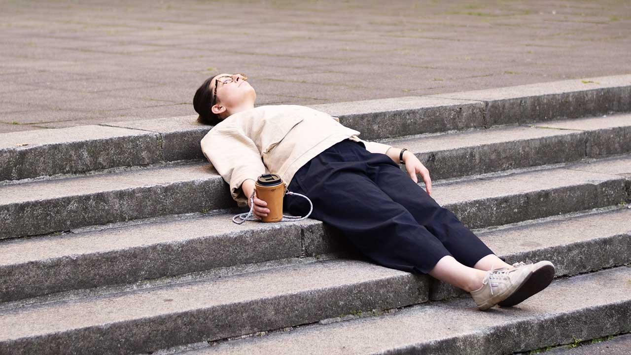 junge Frau ruht sich liegend auf einer Treppe auf