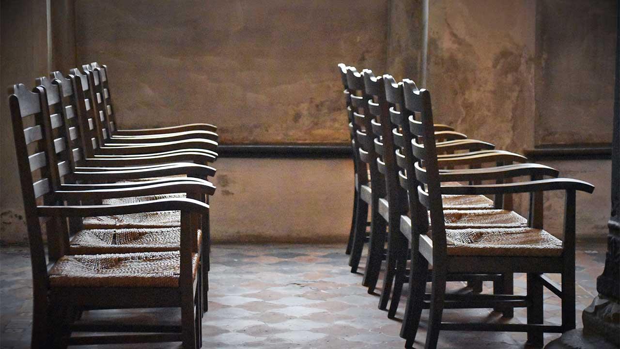 Im Innern eines etwas dunklen Raum mit leeren Stühlen