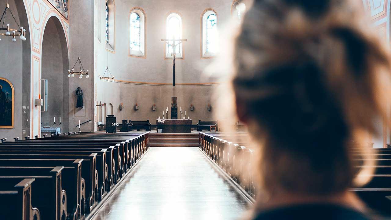 Rückansicht einer Frau, welcher in einer Kirche in München steht