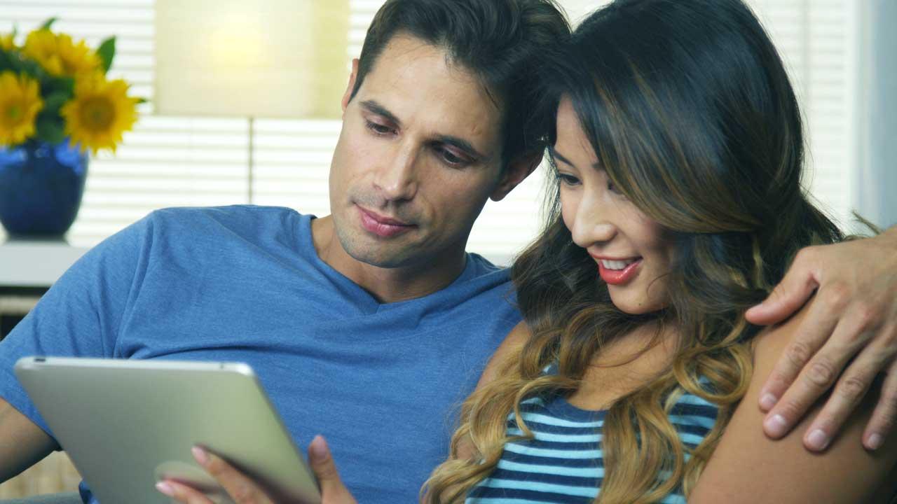 Ehepaar nutzen zusammen ein Tablet und sitzen auf einen Sofa