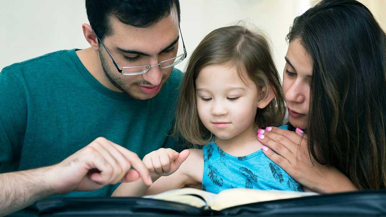 Eltern mit Kind lesen in einem Buch