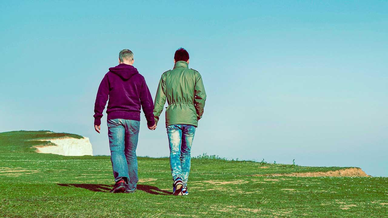 Zwei homosexuelle Männer spazieren zusammen bei einem Kliff in England