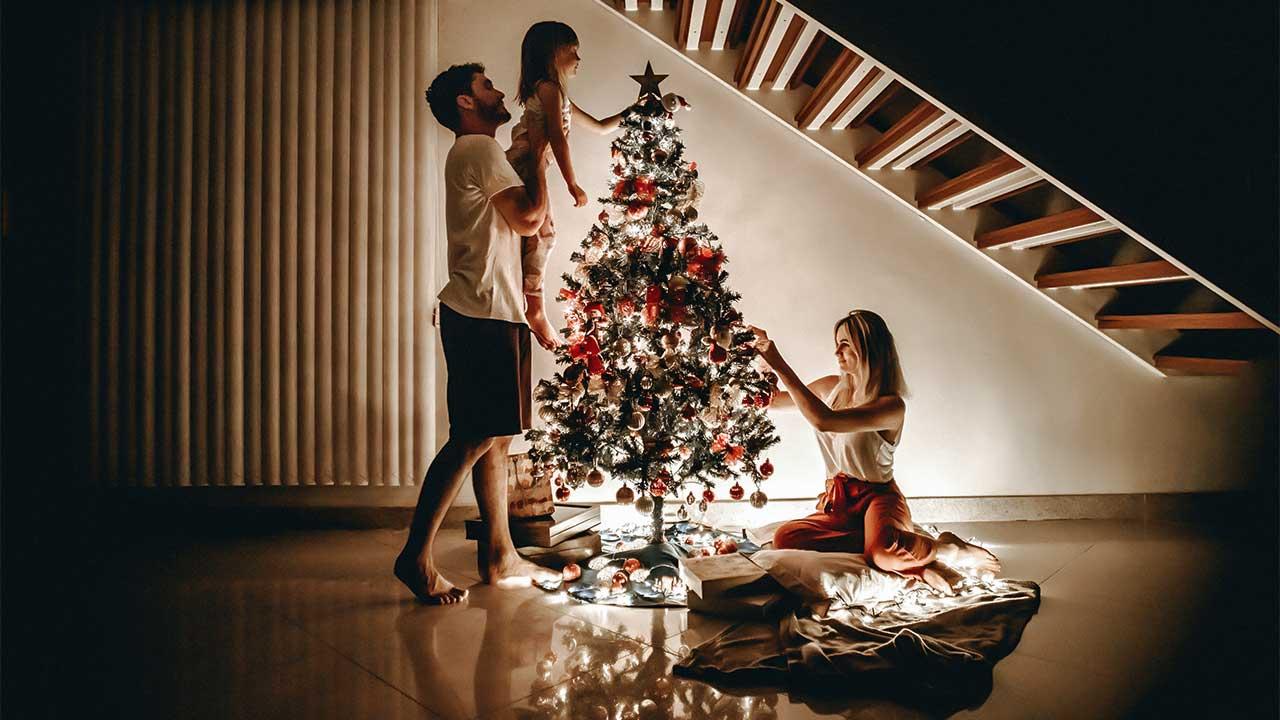 Eltern mit ihrem Kind schmücken einen Weihnachtsbaum