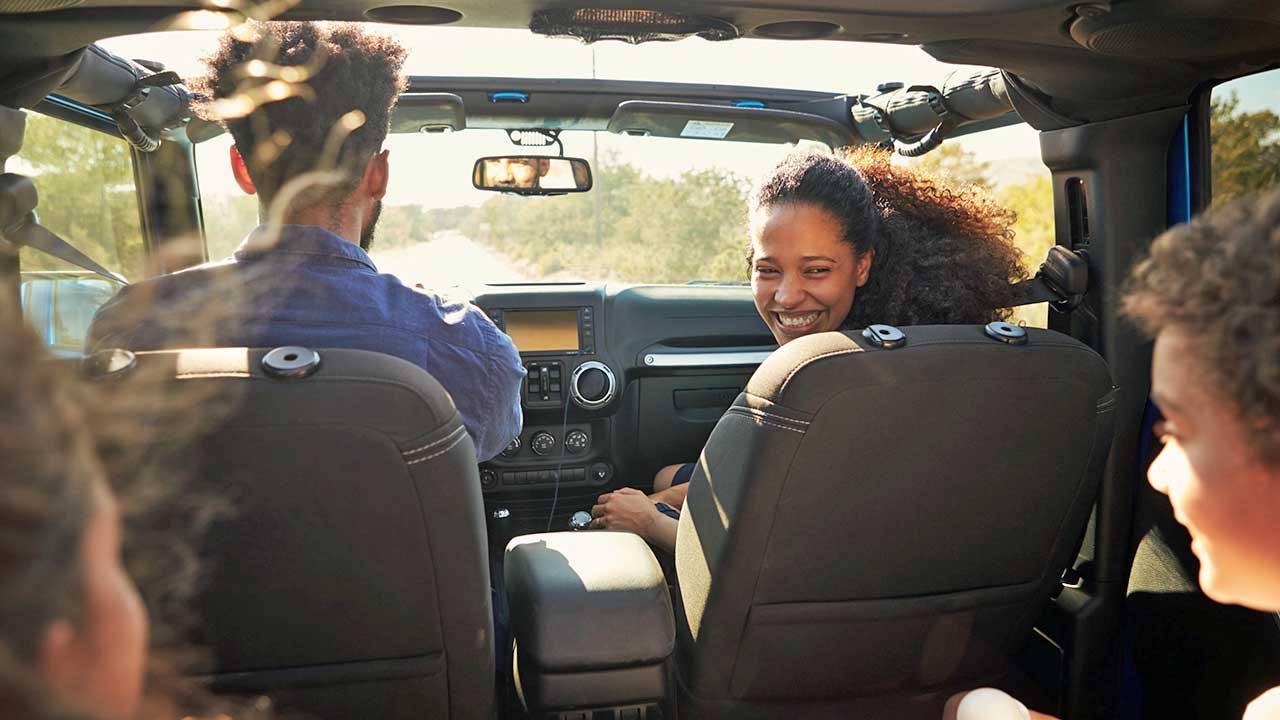 Blick ins Innere eines Autos, wo eine vierköpfige Familie drinsitzt