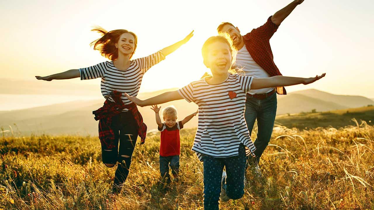 Familie rennt über ein Feld und spielt Flieger