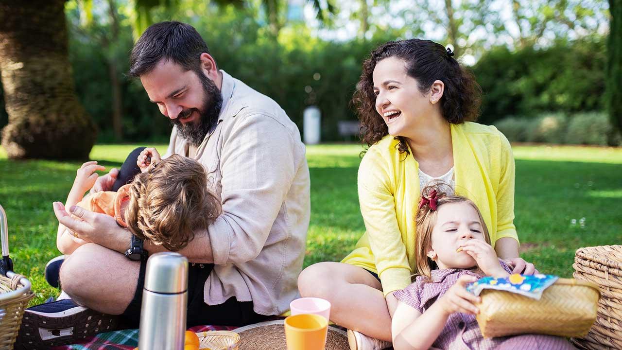 Familie mit zwei Eltern und zwei Kindern beim Picknick