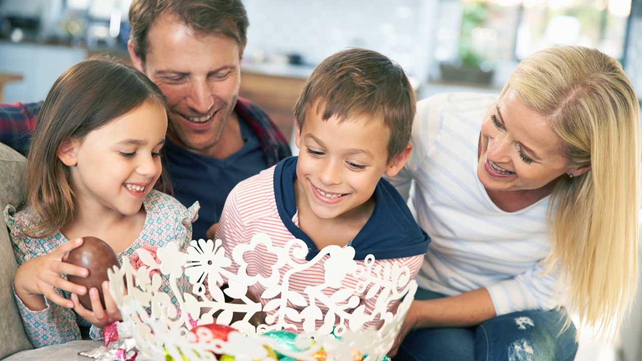 Eltern und Kinder geniessen harmonische Zeit und Schokoladeeier zusammen