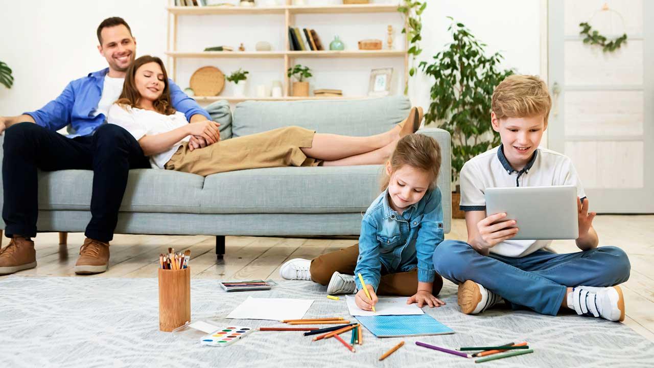 Eltern entspannen auf dem Sofa, die Kinder vor dem Sofa sind zufrieden und beschäftigt
