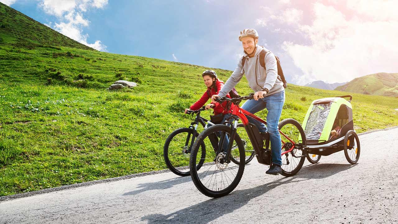 Paar mit Kleinkind unterwegs per E-Bike