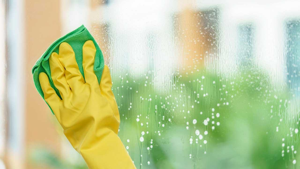 Weibliche Hand in Gummihandschuh und mit Lappen putzt Fenster