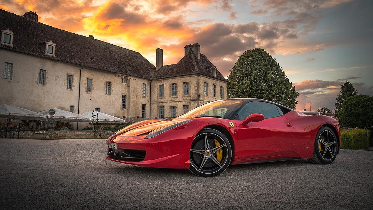 Ein roter Ferrari steht parkiert auf der Strasse.