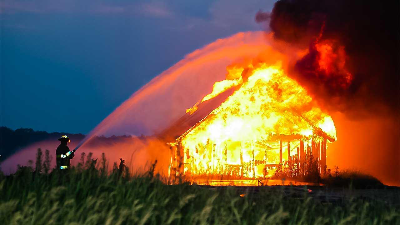 Feuerwehrmann löscht ein brennendes Haus in einem Feld